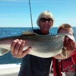 women holding 14 lb lake trout