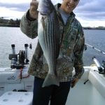 happy youngster with striped bass