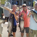 family holding salmon caught with Ace Charters