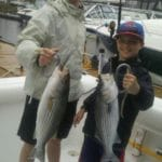 Two brothers holding their stripers